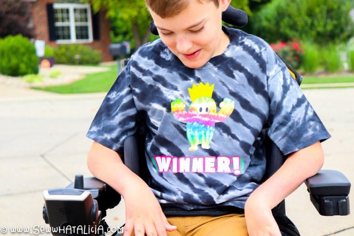 pictured boy in wheelchair with black tie dye shirt that reads winner. shirt also has a tie dye character from the game fall guys