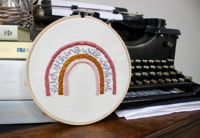 embroidered rainbow with text reading everything will work out, antique typewriter in background