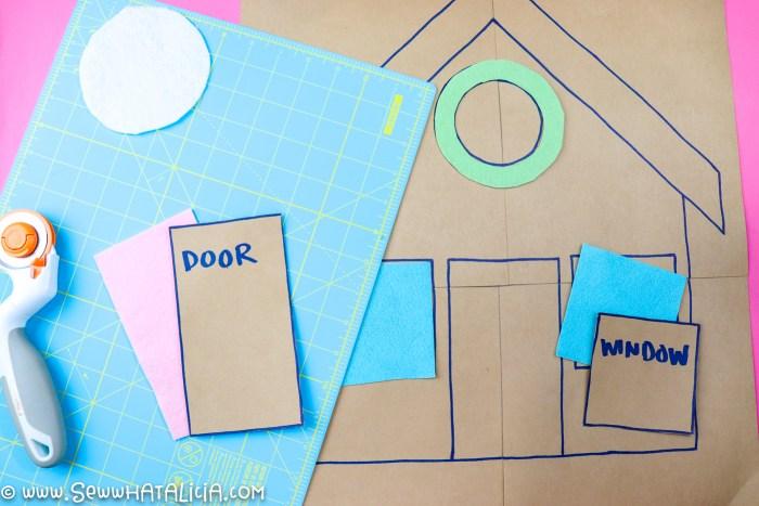 paper gingerbread house pattern, blue cutting mat, cut felt pieces