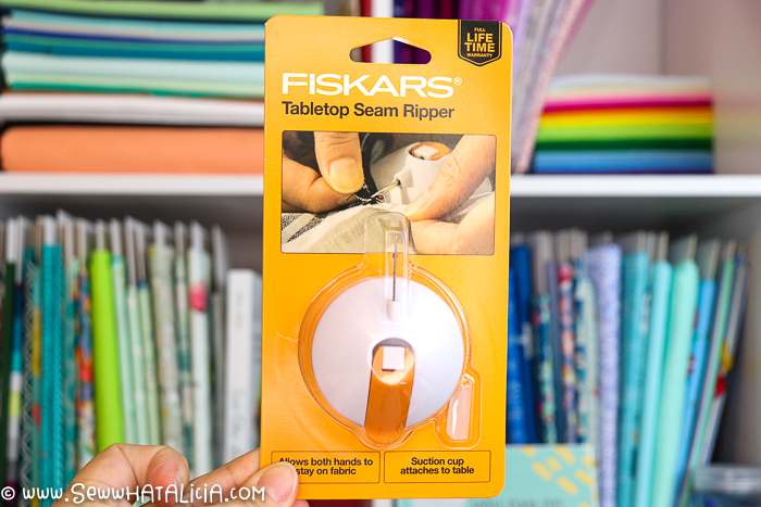 fiskars tabletop seam ripper held by hand with fabric in the background