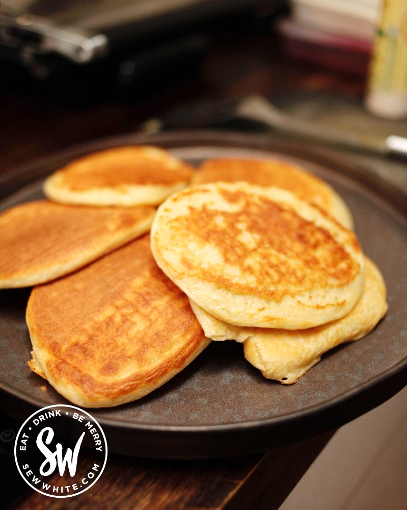 A pile of Scotch Pancakes on a black plate