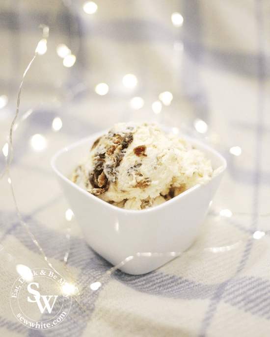 Easy Christmas Pudding Ice Cream using leftover christmas pudding. Scoops of the no churn ice cream in a bowl surrounded by fairy lights.