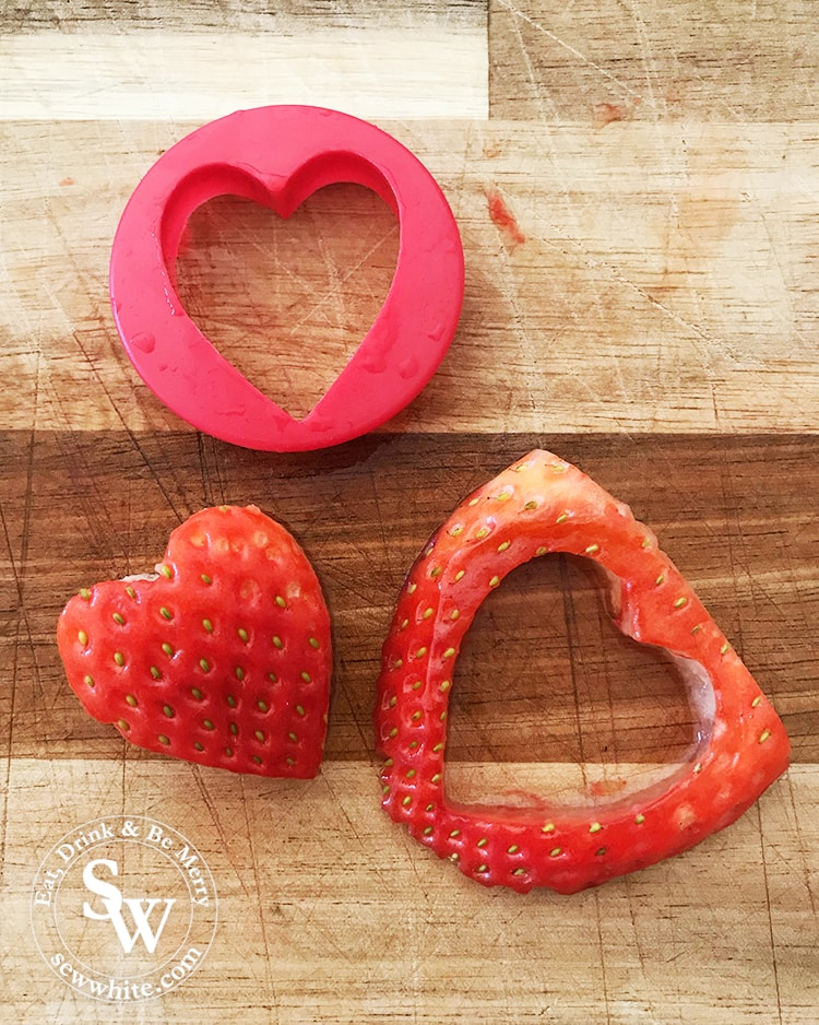Using a cookie cutter to cut out hearts from strawberries