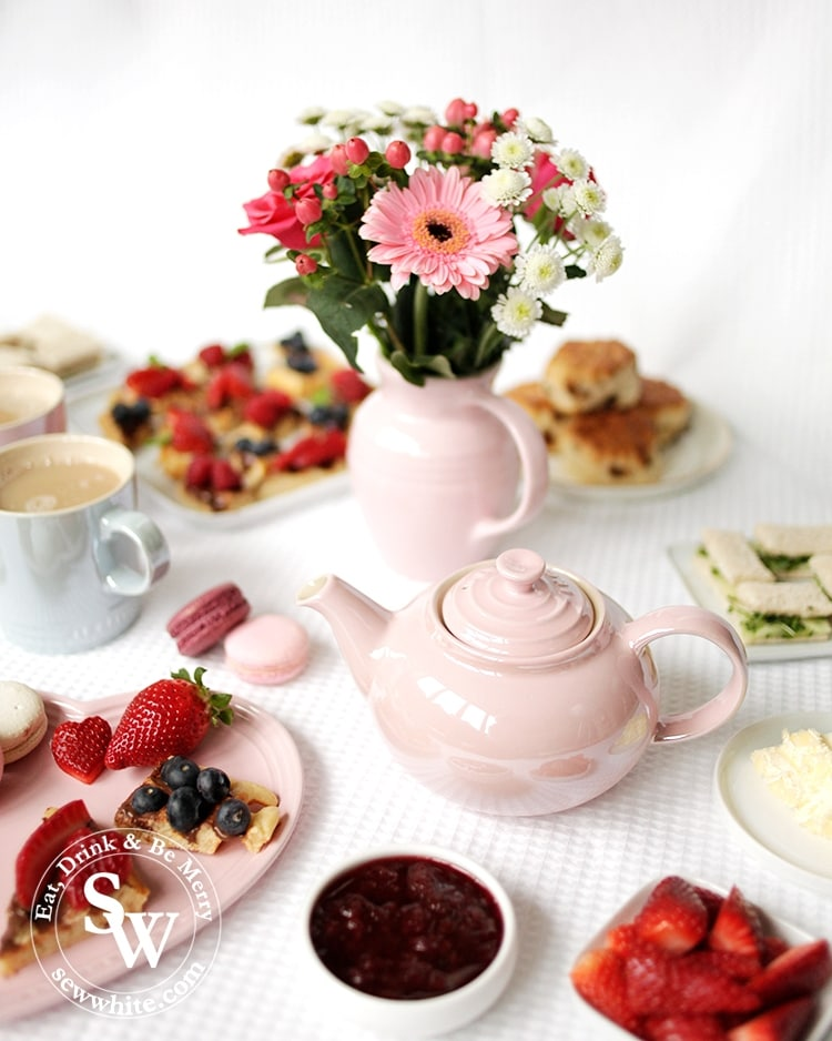 Afternoon tea served with the chiffon pink glace teapot served with lots of freshly baked treats and fresh fruit.