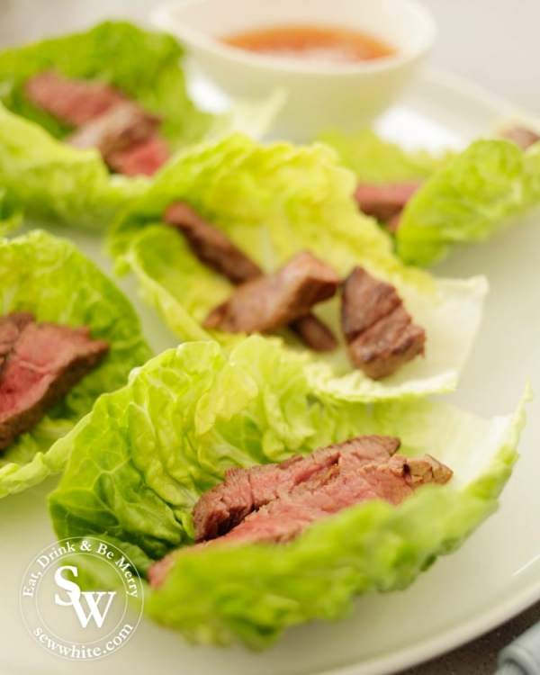 Serving the beef slices for the Vietnamese Inspired Beef Salad Bites in lettuce leaves