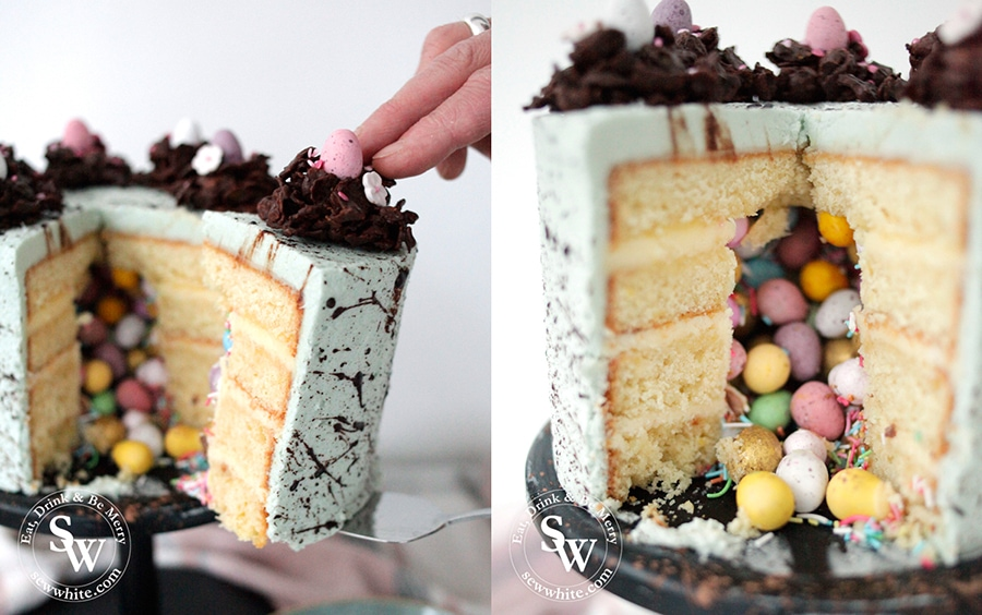 The first slice being taken out of the Speckled Easter Pinata Cake with coloured eggs tumbling out