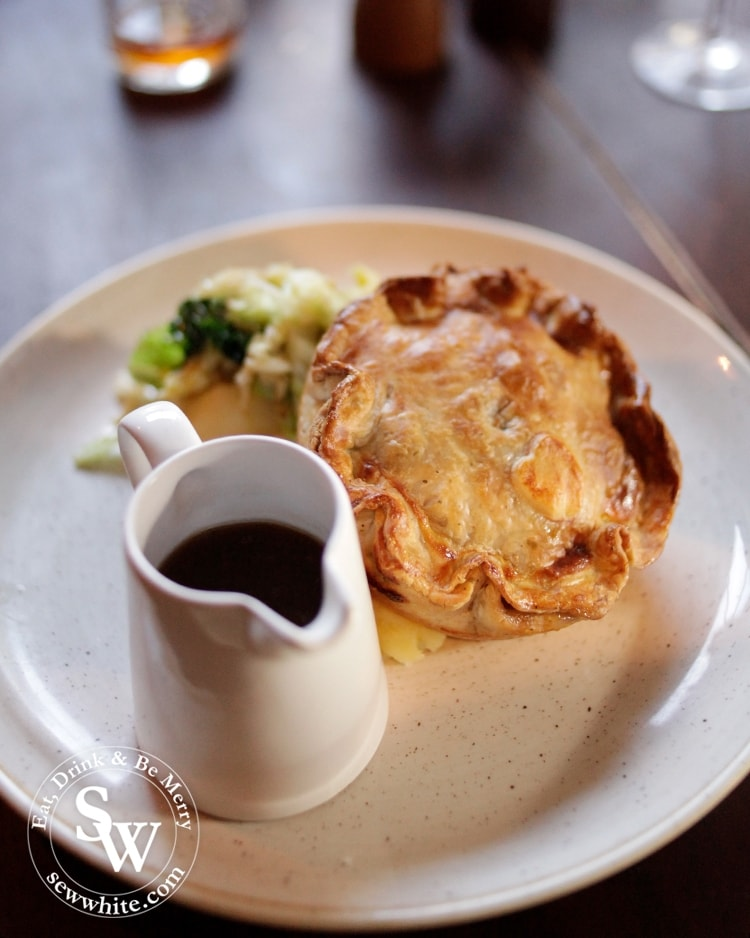 The incredibly impressive golden pastry crust pie served with a little jug of gravy at the Hand in Hand Wimbledon