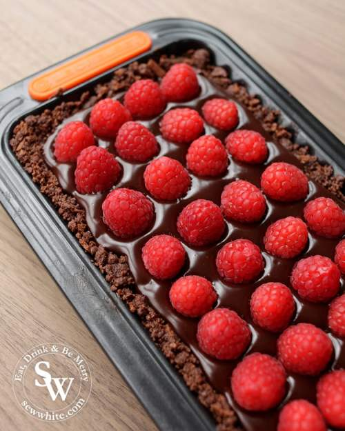 Studded raspberries on a bed chocolate truffle bourbon biscuit base