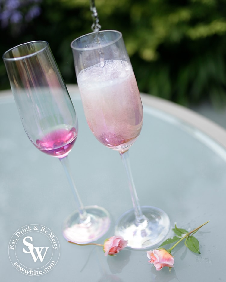 Pouring prosecco into the champagne glasses with elderflower and rose syrup.