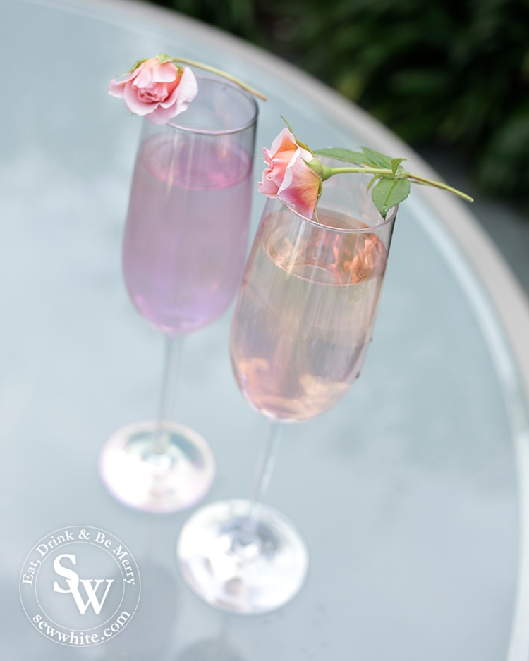 Irredentist purple and pink champagne glasses with roses balanced on top