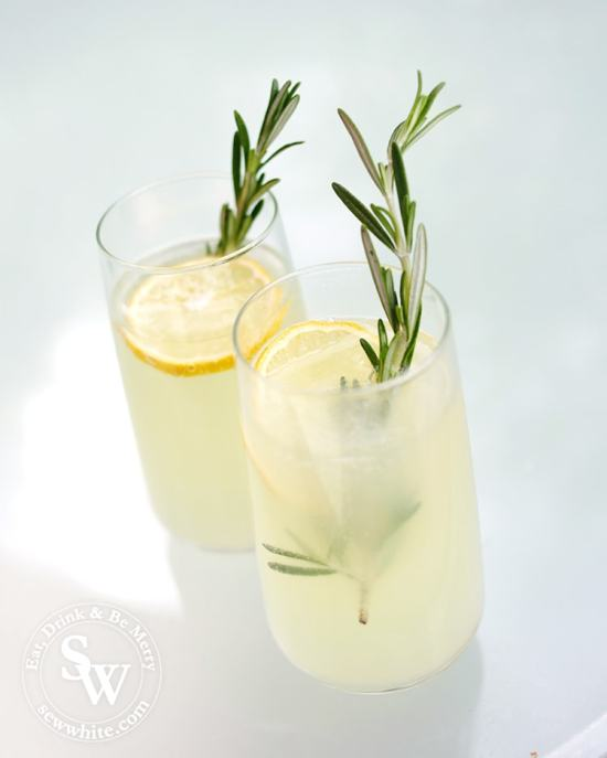 Elderflower and Rosemary Lemonade in tall glasses  with large slices of lemon and a bright green sprig of rosemary.