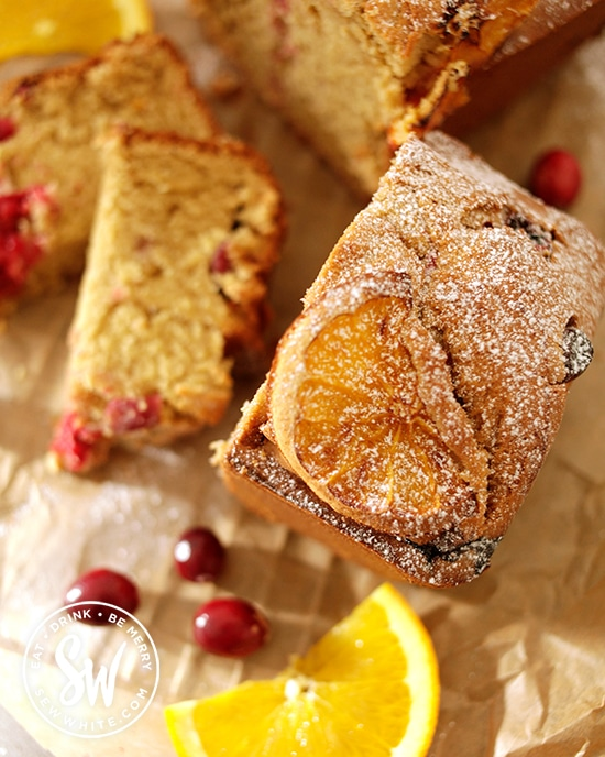 cranberry and orange loaf with baked orange on top dusted with icing sugar ready to serve surrounded by fresh cranberries.
