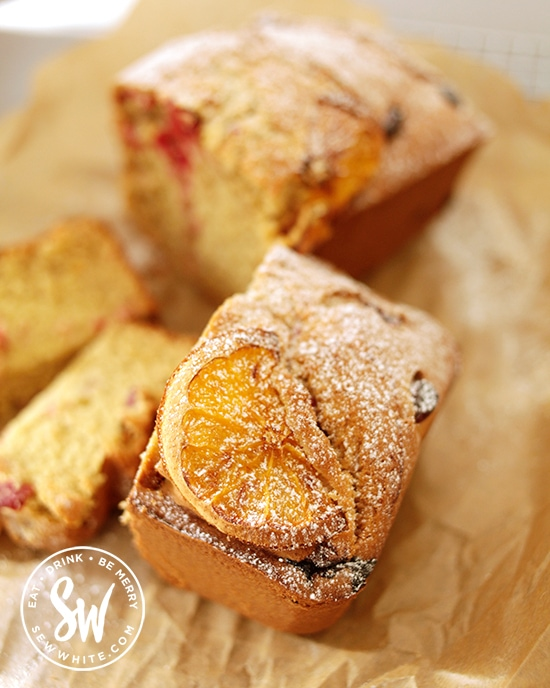 Golden caramelised orange slice on top of a cake dusted with icing sugar.