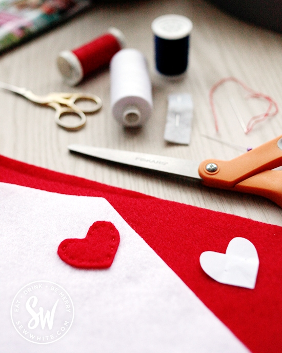 Cutting out a red heart out of felt for the stamp on the felt envelope.