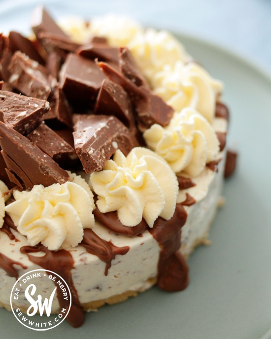 Toblerone Cheesecake with drizzled chocolate, cream swirls and Toblerone pieces on top