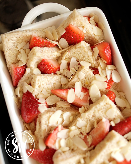 Fresh Strawberry Bread and Butter Pudding topped with flaked almonds ready for the oven.