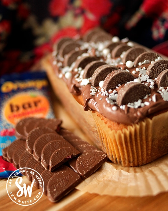 Chocolate Cranberry Cake next to a Terry's chocolate orange bar and topped with mini chocolate orange segments