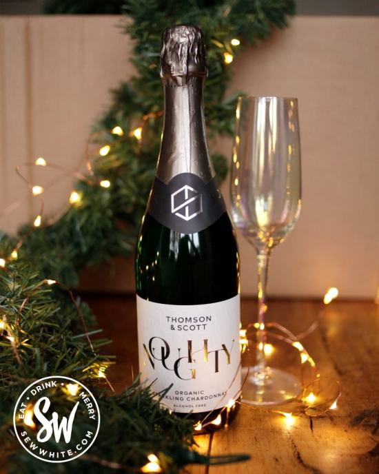 Bottle of Noughty Organic alcohol-free sparkling wine in the drink gift guide list next to a garland of green with fairy lights and champagne glass.