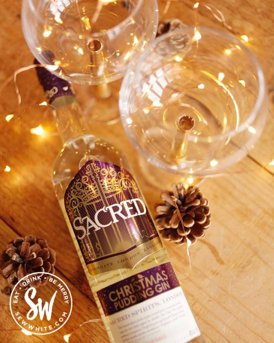 top view of Sacred gin bottle lying down with fairy lights and pinecones