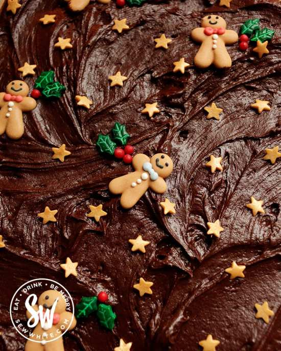 Old School Chocolate Traybake for Christmas with chocolate fudge icing decorated with gingerbread men, gold stars and holly sprinkles