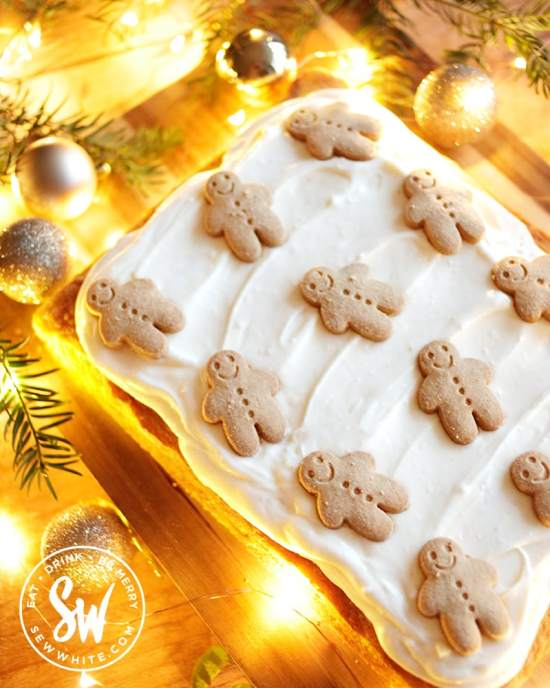 easy gingerbread traybake topped with cream cheese frosting and gingerbread men.