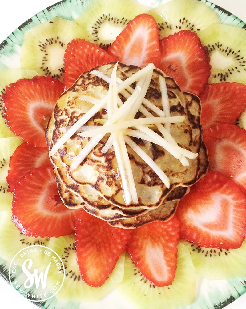Apple pancakes topped with grated apple on top of a bed of fresh strawberries and kiwi.