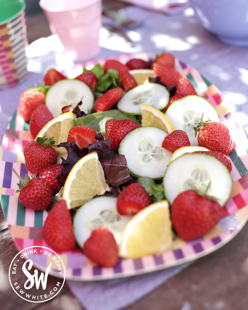 pimm's salad on a bright pink and purple plate. Slices of orange, cucumber, strawebrries and salad. pimms sald