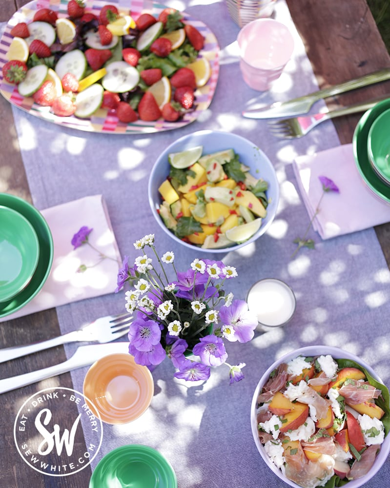 picnic table with purple flowers and multiple salads including the pimm's salad