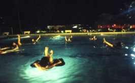 """Western expatriates take a break from humanitarian relief operations to practice """"aquatic yoga"""" at a plush club swimming pool off limits to ordinary Congolese people. Just one of the many perks of relief work in """"exotic"""" foreign war zones. – Photo: Keith Harmon Snow, 2007"""