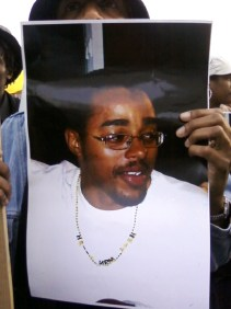 Lovelle Mixon is pictured as friends and family remember him on a poster carried at a rally Wednesday, March 25, outside the apartment building where he died.
