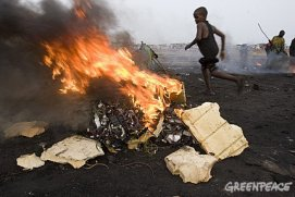 Electronic waste – discarded computers, cell phones and the like – from the U.S. and Europe poisons children in Ghana who earn a living in the dump, burning it and extracting copper and other valuable materials with their bare hands. – Photo: Greenpeace