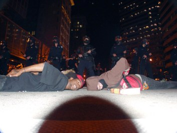 "Tensions have remained high since war in Oakland broke out at 2 a.m. on New Year's when BART police murdered Oscar Grant. Here, during the first rebellion, on Jan. 7, young people taunt the cops by lying face down, assuming Oscar's position when he was executed, in a pose that conveys the message, ""We are all Oscar Grant."" – Photo: Dave Id, Indybay"