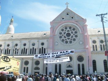 """A large banner in front of Haiti's national cathedral reads, """"[Father] Jery, you left us but the struggle continues."""" – Photo: ©2009 Jean Ristil, Haiti Information Project"""
