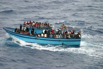 """Africans are so intent on reaching Europe that they pay at least $1,200 to crowd aboard a little boat to cross the Mediterranean. Expecting the trip to take only a day, they carry no food or water. Many die when their journey lasts as long as five days. The fins of the """"big fish"""" that follow the boats can be seen in the water."""
