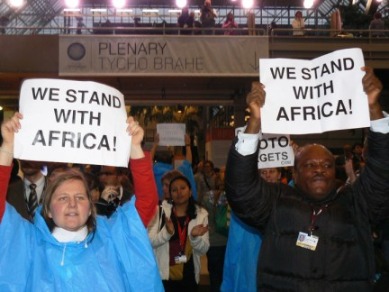 "Chanting and ""signing,"" ""We stand with Africa!"" people inside the Bella Center calling for Kyoto targets to be met shut down the climate talks for several hours Monday. – Photo: Nasseem Ackbarally, IPS"