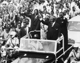 "The original caption for this photo, taken June 1, 1963, reads: ""Nairobi, Kenya – Waving his 'wisk' the newly-elected Premier of Kenya, Jomo Kenyatta (R, foreground), greeted throngs of cheering citizens as he rode through the streets of Nairobi. Accompanying Kenyatta are Tom Mboya (L), Minister of Justice and Constitutional Affairs; A. Oginga Odinga, Minister for Home Affairs; and James S. Gichuru, Minister for Finance. The motorcade was part of the National Holiday celebrations which marked the start of internal self-government for the African nation."" Photo: © Bettmann/CORBIS"