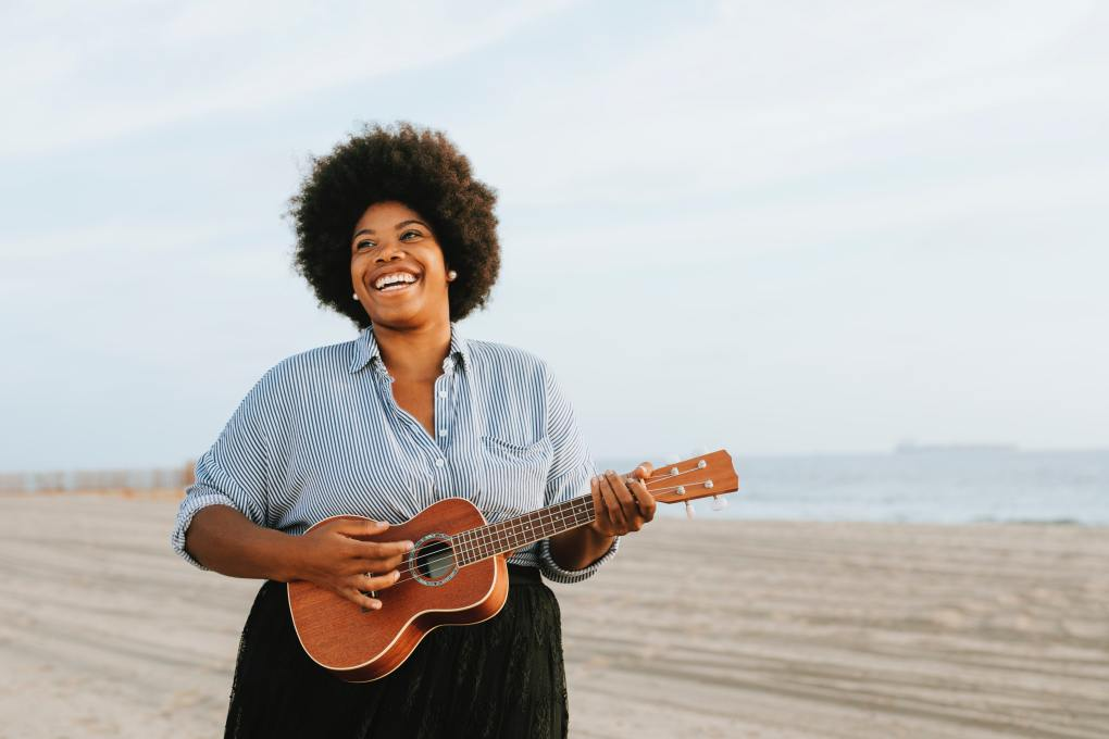 Lady playing guitar on a beach. Representing guitar and strings lessons at SFE Music School