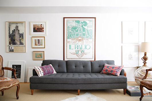 unique framed prints above tufted gray sofa with colorful pilows / sfgirlbybay