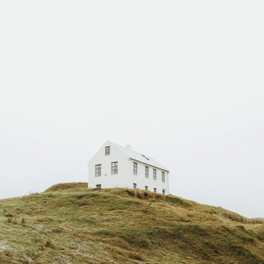 white house on a grassy hill in iceland / sfgirlbybay