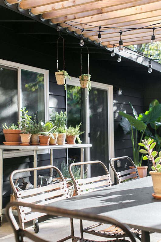 my black house with wood pergola and industrial string lights / sfgirlbybay