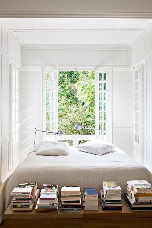 white bed with stacks of books / sfgirlbybay