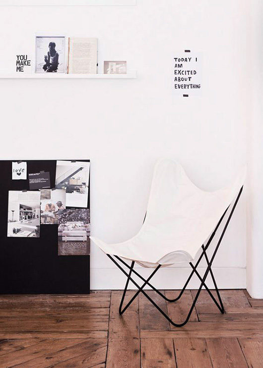 white butterfly chair in black and white room with wood floors / sfgirlbybay