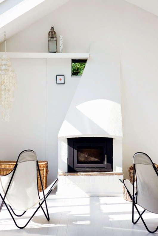 a pair of white butterfly chairs with black frames in front of a fireplace / sfgirlbybay
