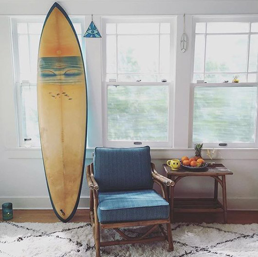 moroccan rug with yellow surboard and pops of cool blues and hints of pale peachy blush and orange in white room with windows / sfgirlbybay