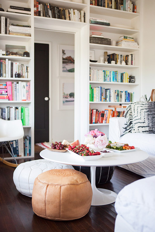 low white pedestal coffee table with fruit and cheese plates on top and three leather moroccan floor poufs underneath / sfgirlbybay