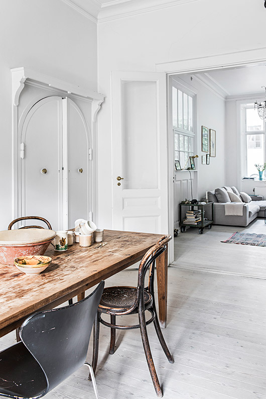 farm table with mismatched chairs in copenhagen home with white walls / sfgirlbybay