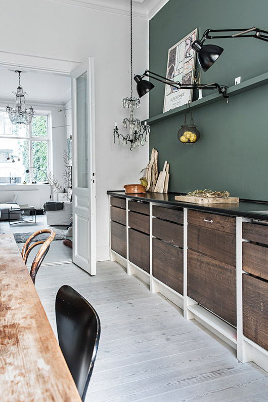 danish kitchen with black lamps and chandelier with dark wood drawers / sfgirlbybay