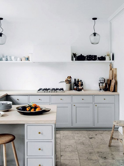 gray kitchen cabinets with natural wood countertops and glass hanging pendant lamps / sfgirlbybay