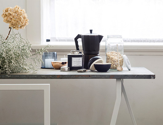 sleek table with muted floral arrangement and vintage stove-top black espresso maker and jar of oats / sfgirlbybay