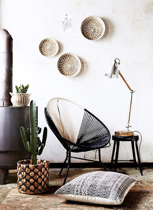 modern black and white woven acapulco chair with woven white bowls on wall / sfgirlbybay